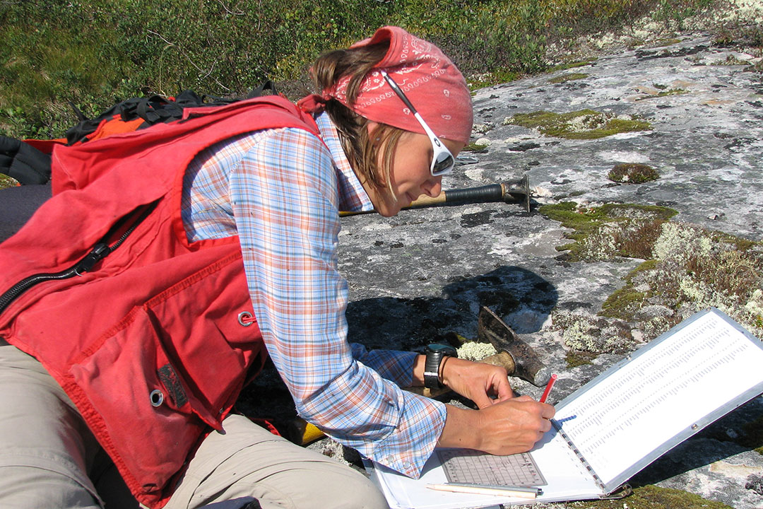 Woman Geologist Note-taking on a Rock Outdoors